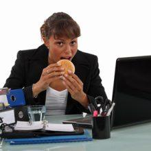 Tips and advice for eating at your desk etiquette - office table manners - photo of girl eating at desk