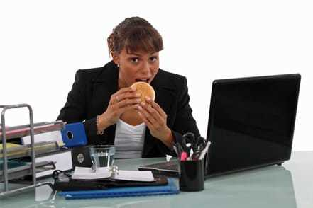 Tips and advice for eating at office desk etiquette - photo of girl eating at desk